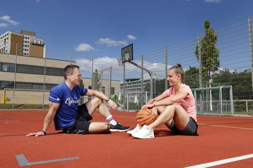 Ein Mann und eine Frau sitzen auf einem roten Sportplatz