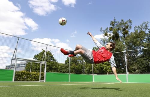 Ein Fußballer tritt im Sprung nach einem Ball